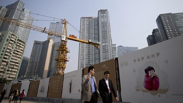 Office workers walk past China Dream propaganda boards, showing messages pushed by current Chinese President Xi Jinping's administration, on display near a construction site in Beijing on Oct. 8. The country's leaders are meeting this weekend to chart China's economic course.