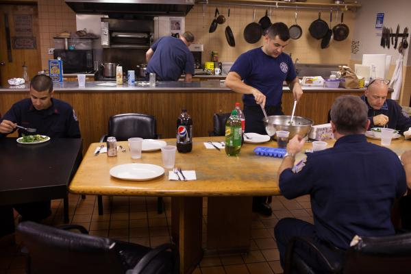 Left to right, Andres Godoy, John Palombini, Kamil Mizinski, Greg Kemp and Capt. Bill Laban, have dinner at the 16th Street Firehouse. This day was Godoy's second day at the house. For Kemp, it was his 24th year.