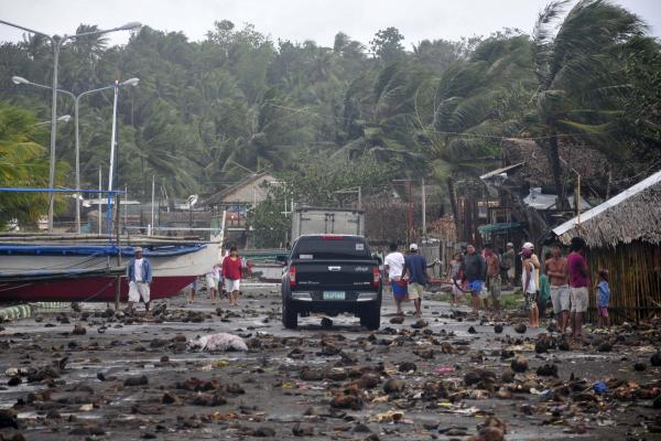 Debris litters a road in a coastal village in Legazpi City, Philippines, after a storm surge brought about by Typhoon Haiyan on Friday. The storm forced millions of people to flee to safer ground, damaging power lines and blowing apart houses.