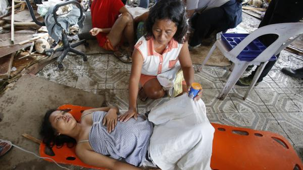 A woman comforts a pregnant relative suffering labor pains at a makeshift birthing clinic in typhoon-battered city of Tacloban, Philippines on Nov. 11.