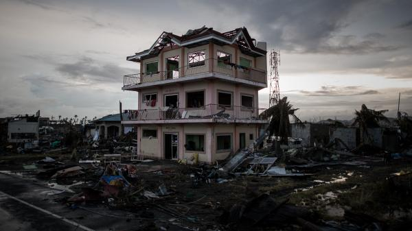 The sun sets behind a house damaged by Typhoon Haiyan outside the hard-hit city of Tacloban. The Philippines has gotten better at preparing for typhoons, but remains extremely vulnerable.