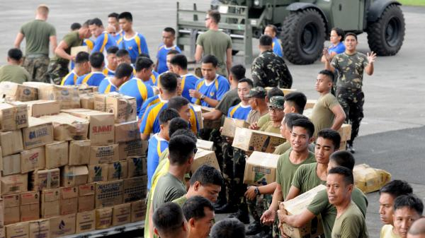 U.S. and Filipino military personnel prepare relief goods in Manila for transport to the hard-hit city of Tacloban.