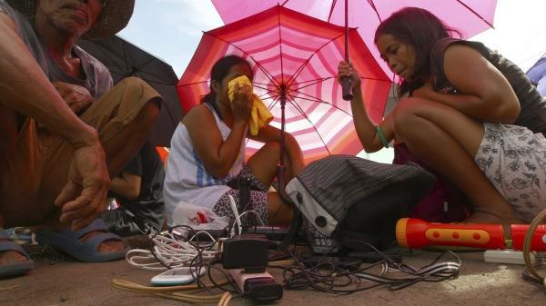 Typhoon survivors line up Wednesday to charge their mobile phones using power outlets provided by a cellular service provider in Tacloban, Philippines.