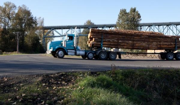 A truck carries logs across the Columbia River to the Port of Longview, where they are loaded onto ships.