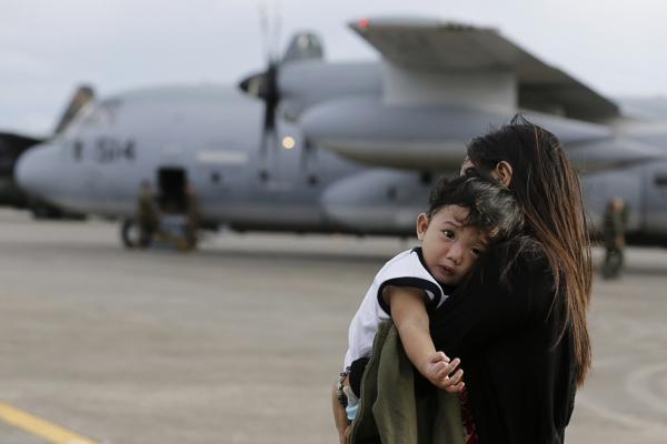 A mother carries her child after leaving a U.S. air carrier at Manila's military airport from Tacloban.