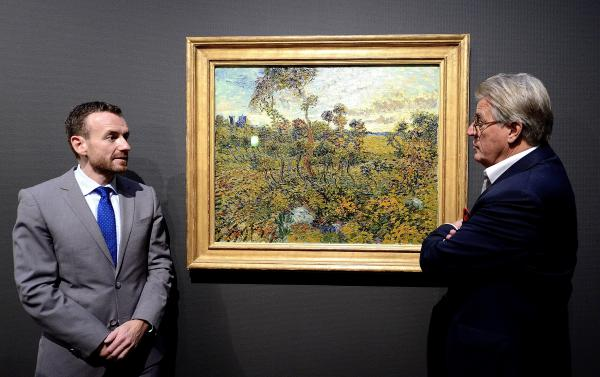 Museum director Alex Rueger (L) and Dutch artist Jeroen Krabbe stand in front of Vincent van Gogh's long-lost <em>Sunset at Montmajour</em> at the Van Gogh Museum in Amsterdam. The 1888 landscape painting from the height of the Dutch master's career had been abandoned for years in a Norwegian attic on the belief that it was a forgery.