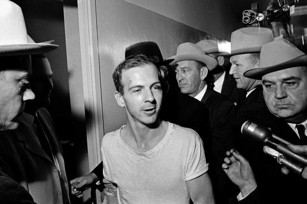 Surrounded by detectives, Lee Harvey Oswald talks to the press as he is led down a corridor of the Dallas police station, for another round of questioning in connection with the assassination of Kennedy. Oswald, who denied any involvement in the shooting, was formally charged with murder.