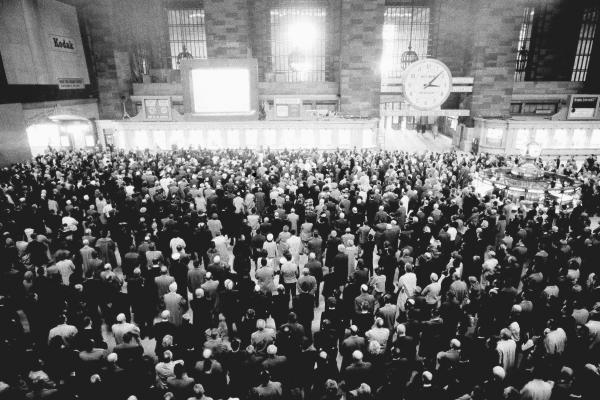 Spectators at Grand Central Terminal in New York City watch a large-screen television presentation of Kennedy's funeral on Nov. 25. The funeral's sounds created a churchlike atmosphere in the station's vast upper concourse.