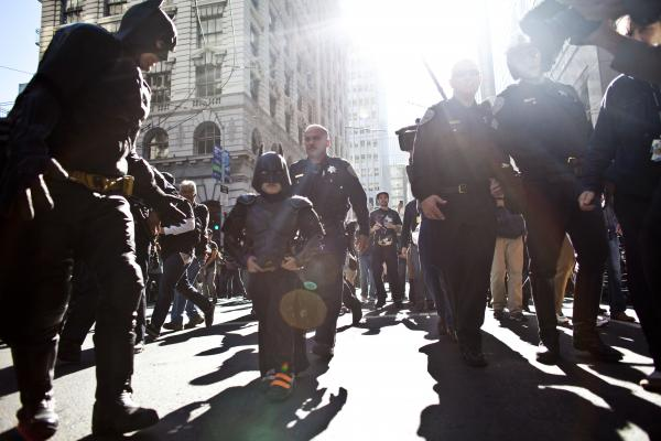 Police escort Batkid and Batman after they arrest The Riddler.