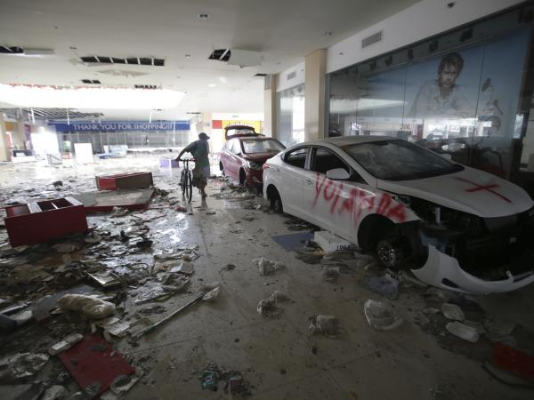 A Filipino man walks inside a mall that has been flooded and reportedly looted after Typhoon Hayian hit Tacloban. Yolanda, seen here spray-painted on an abandoned car, is the name given to the typhoon by Philippine authorities.