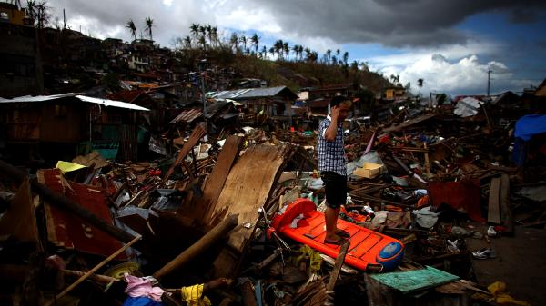 A Filipino man stands on a massive pile of wreckage in Tacloban city on Saturday. The city was devastated one week earlier as Typhoon Haiyan tore through.