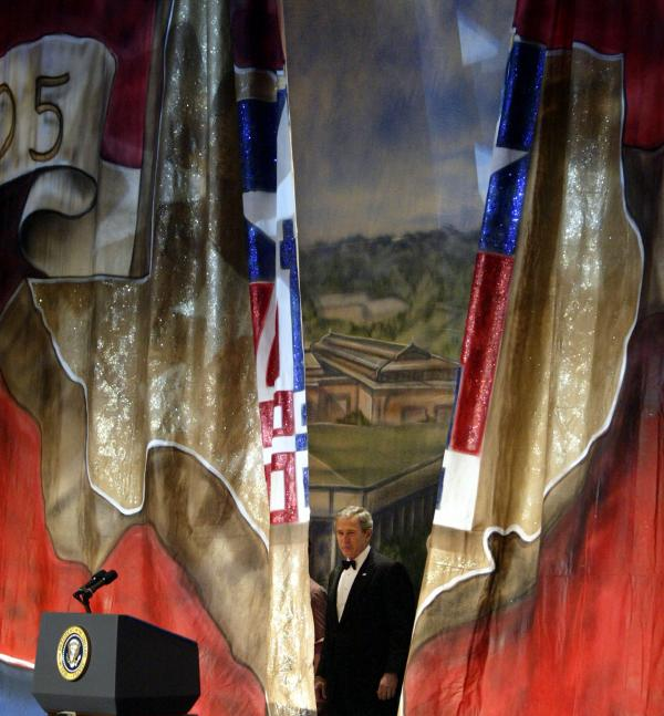 President George W. Bush appears behind a curtain painted with the outline of Texas at the Black Tie and Boots Inaugural Ball in Washington, D.C., on Jan. 19, 2005.