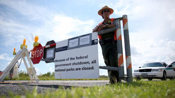 U.S. Park Ranger Mirta Maltes stands near the road-closed sign leading to the Everglades National Park on Oct. 7 in Miami.