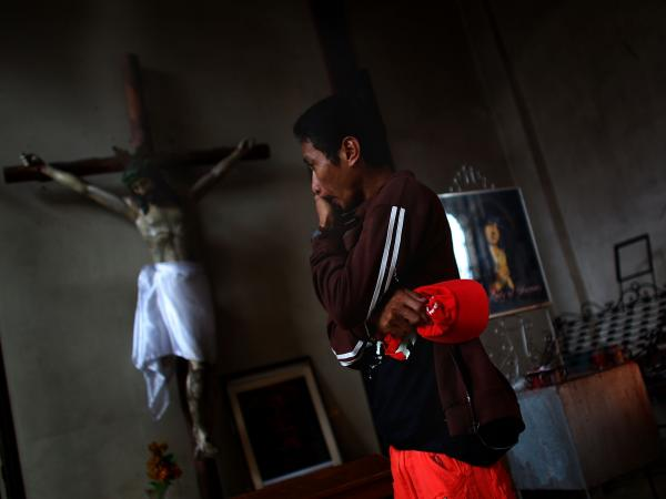 A Filipino man wipes the tears from his eyes on Sunday before morning Mass at Santo Nino church.