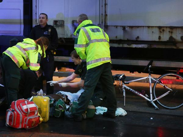 A cyclist receives emergency medical treatment after being involved in an accident with a truck on Monday in London.