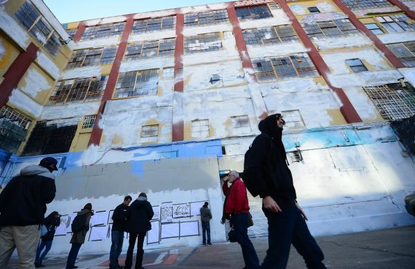 "People walk in front of New York's graffiti iconic spot ""5Pointz,"" after the building was painted white in New York."