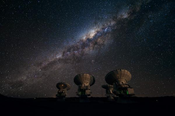 "Part of the <a href=""http://www.eso.org/sci/facilities/alma.html"">ALMA array</a> on the Chajnantor plateau of Chile points skyward to the Milky Way, our own galaxy. The <a href=""http://www.eso.org/public/images/alma-jfs-2010-10/"">center of our galaxy</a> is visible as a yellowish bulge crossed by dark lanes, which are themselves huge clouds of interstellar dust."