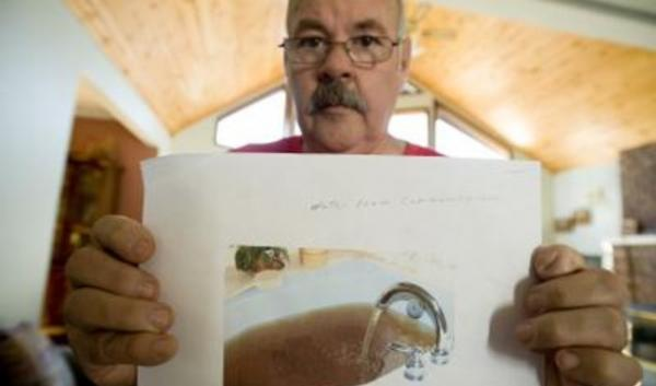An environmental group is suing a mining company in Clark County for water pollution. Local resident David Rogers shows a photo of his bathtub filled with well water.