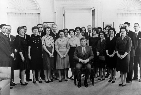 President John F. Kennedy poses with his staff in the Oval Office. The group pooled their funds to buy Kennedy his presidential chair. Jean Lewis stands over Kennedy's left shoulder. (Courtesy JFK Library)