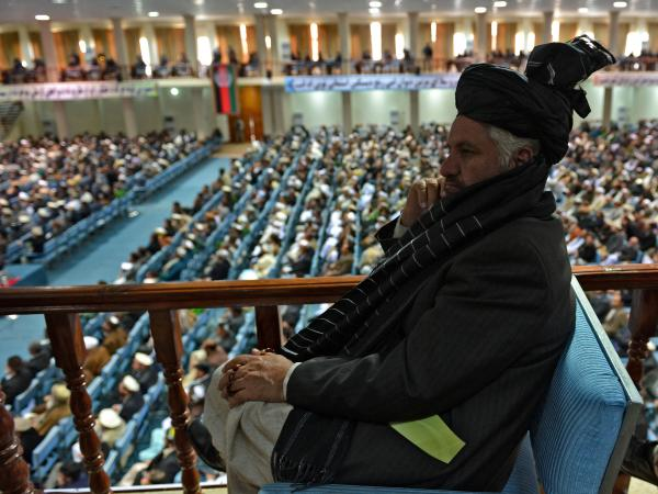 A member of the Afghan Loya Jirga listens as the more than 2,000 elders begin debating a proposed U.S.-Afghan security pact on Thursday in Kabul.