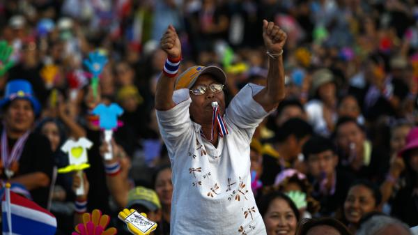 An anti-government protester blows her whistle during a rally Wednesday at Democracy Monument in Bangkok.