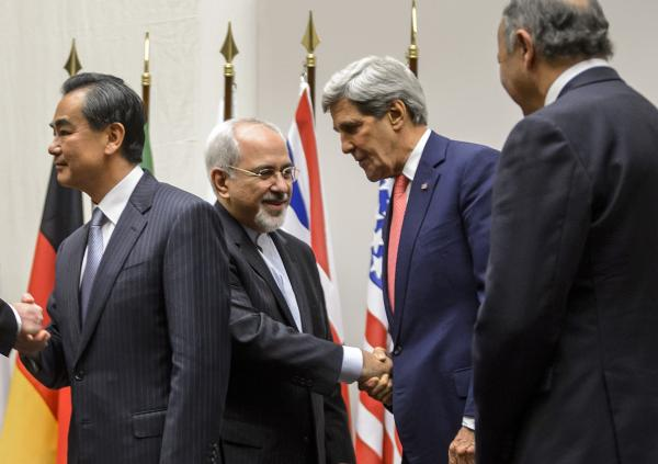 Iranian Foreign Minister Mohammad Javad Zarif (second from left) shakes hands with U.S. Secretary of State John Kerry next to Chinese Foreign Minister Wang Yi (far left) and French Foreign Minister Laurent Fabius (far right) after a statement on early November 24, 2013 in Geneva.