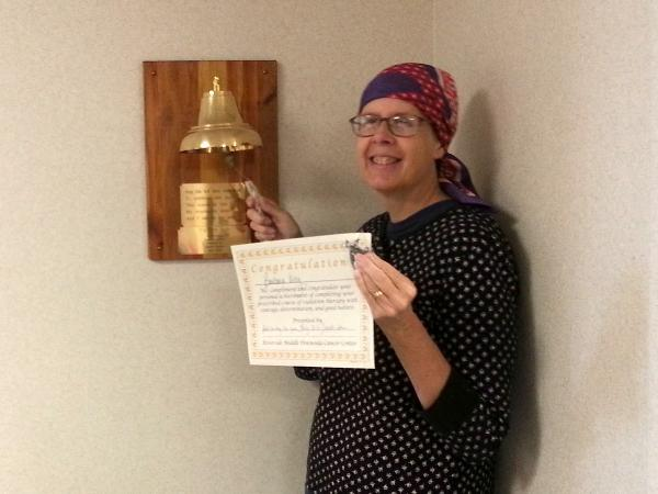 "Barbara King rings the ""victory bell"" and holds up a certificate celebrating her completion of 25 external radiation treatments."