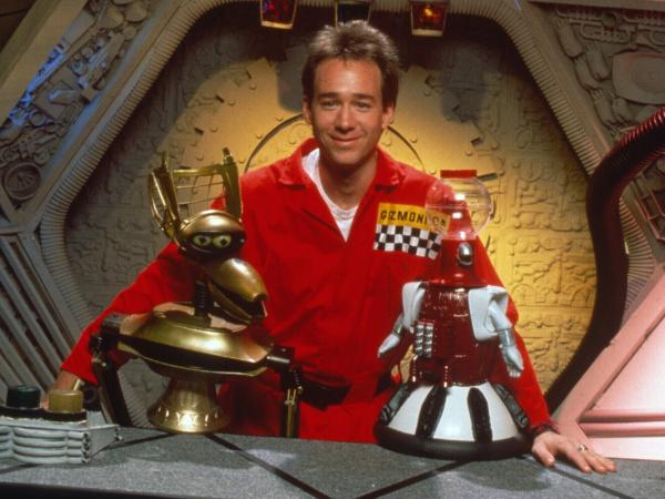 "Joel Hodgson poses with Crow T. Robot and Tom Servo, two of his ""robot friends."""