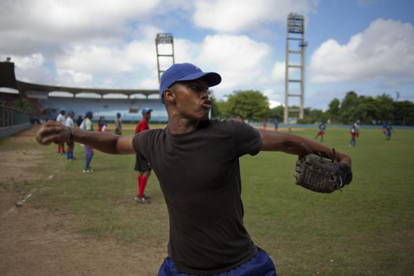 A player for Havana's Industriales baseball team winds up to throw a ball during a training session in Havana on Sept. 27. Cuba recently lifted a ban on its athletes' signing contracts to play overseas professionally.