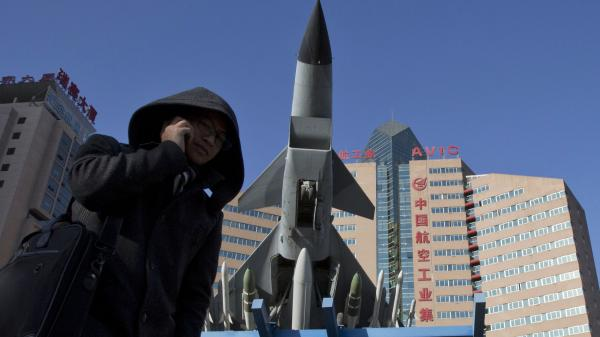 Concerns over China's air defense claims led Secretary of Defense Chuck Hagel to call Japan's defense minister Wednesday. Here, a man makes a call near a replica of a Chinese fighter jet displayed in Beijing Wednesday.