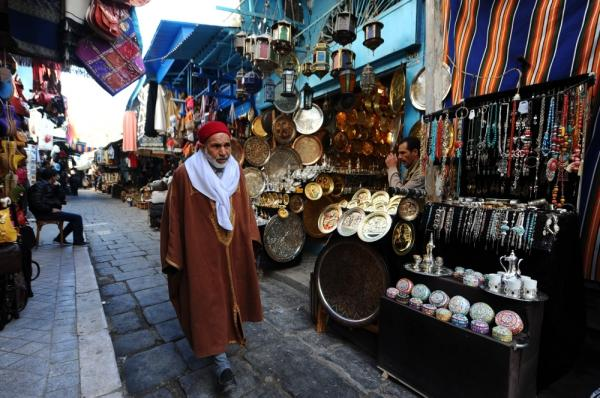 "A Tunisian man walks through a medina in February. Today, the shops are suffering for lack of tourists. ""The tourism is catastrophic in Tunis today,"" says Said Ayari, who sells handicrafts like traditional pointed leather shoes."