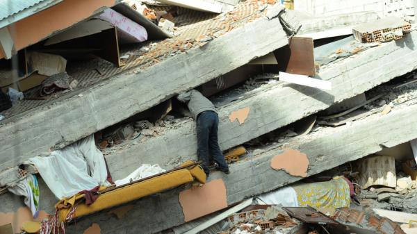 <p>A Turkish men searches through the debris of his collapsed building in Ercis.</p>