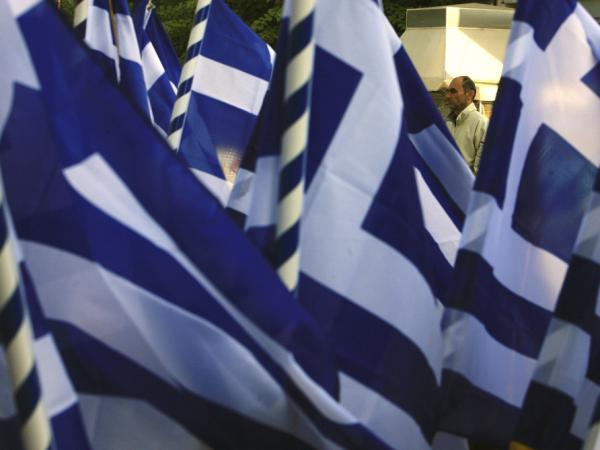 <p>A pedestrian passes a vendor selling Greek flags in Athens on  Wednesday (Oct. 26, 2011). Greece's crushing debts triggered the latest crisis.</p>