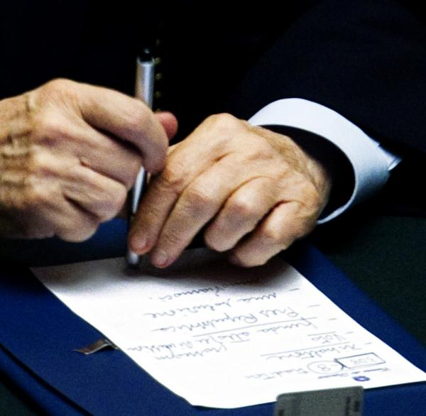 Italian Premier Silvio Belrlusconi holds a pen on a note he wrote during Democratic party leader Pierluigi Bersani's speech on Tuesday.