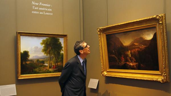 An exhibit at the Louvre Museum in Paris explores American landscape painting. Here, the museum's director, Henri Loyrette, looks at the oil paintings of Thomas Cole (1801-1848), known for his realistic and detailed works.
