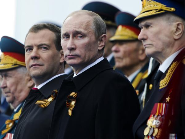 Russian President Dmitry Medvedev (left), Prime Minister Vladimir Putin and World War II veterans watch Victory Day celebrations in Moscow last May. Putin says his proposed military modernization will cost the equivalent of about $770 billion over the next 10 years.