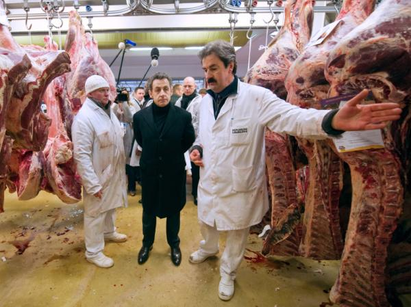 French President Nicolas Sarkozy listens to a butcher during a visit to the butchery pavilion at the Rungis international food market, near Paris, in February.