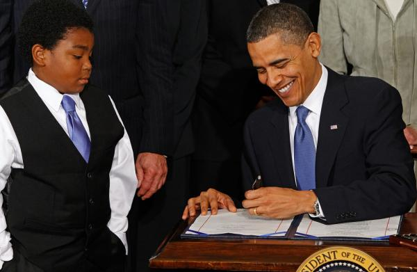 President Obama signs the Affordable Care Act in the East Room of the White House on March 23, 2010. Data suggest that racial attitudes of ordinary Americans shape both how they feel about the health care overhaul and how intense those feelings are. <em></em>