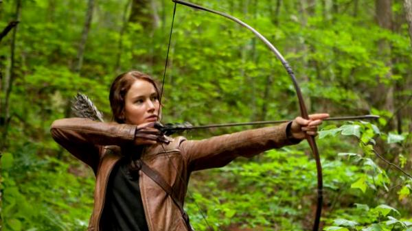Jennifer Lawrence aims an arrow in <em>The Hunger Games</em>. The central character of the film based on Suzanne Collins' books relies on her ability with a bow to survive.