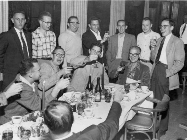 "William Shockley (at head of table) celebrates winning a share of the 1956 Nobel Prize. Gordon Moore (seated far left), Sheldon Roberts (next to Moore), Robert Noyce (middle standing), and Jay Last (far right) are half of the ""Traitorous Eight."""