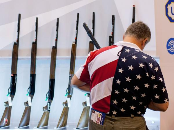 Chris Patrie looks at the Benelli display of shotguns during the NRA annual meetings and exhibits Friday in St. Louis.