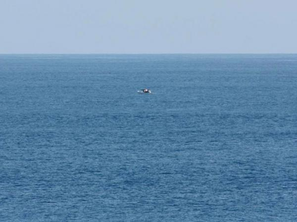 Bird-watcher Jeff Gilligan snapped this photograph of a small boat in distress. Gilligan and others say the cruise ship he was traveling on did not stop to help the stricken craft.