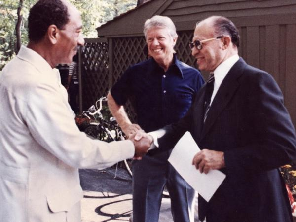 This file photo shows former Egyptian President Anwar al-Sadat (L) as he shakes hands with former Israeli Premier Menachem Begin, as former U.S. President Jimmy Carter looks on 06 September 1978 at Camp David. The meetings led to a treaty between Israel and Egypt.