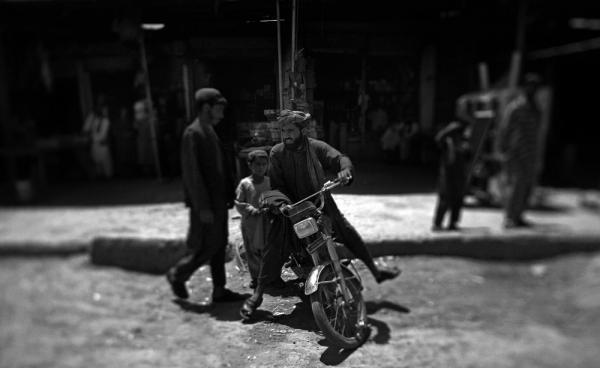 A man rides a motorcycle at a bustling Marjah bazaar. The market was the scene of bitter fighting between U.S. Marines and Afghan insurgents in February 2010.