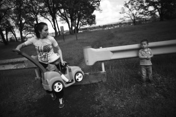 Marine veteran Crystal Turner, a student at Sierra College, holds her daughter, Marley Rose, while she tries to coax her son, Michael, into finishing a walk in the park near their home in Sacramento.