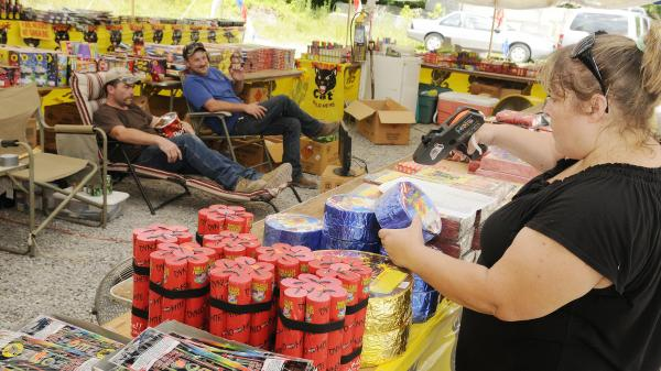 Susan Underwood prices fireworks, while her husband Michael (left) and Clint Simmons pace themselves with a snack and TV last month at their tent along Highway 416 in Sevier County, Tenn. Over in Middle Tennessee, the drought has led city leaders to ban fireworks this year.