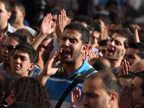 Palestinian demonstrators chant slogans in the West Bank city of Ramallah last month during a protest against a meeting between Abbas and Israel's deputy prime minister.