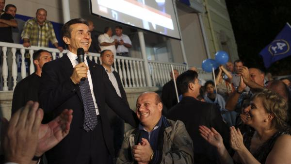 Georgian billionaire and opposition leader Bidzina Ivanishvili (left) reacts with supporters at his office on Monday. Ivanishvili defeated Georgian President Mikheil Saakashvili in the election, clearing the way for a new government.
