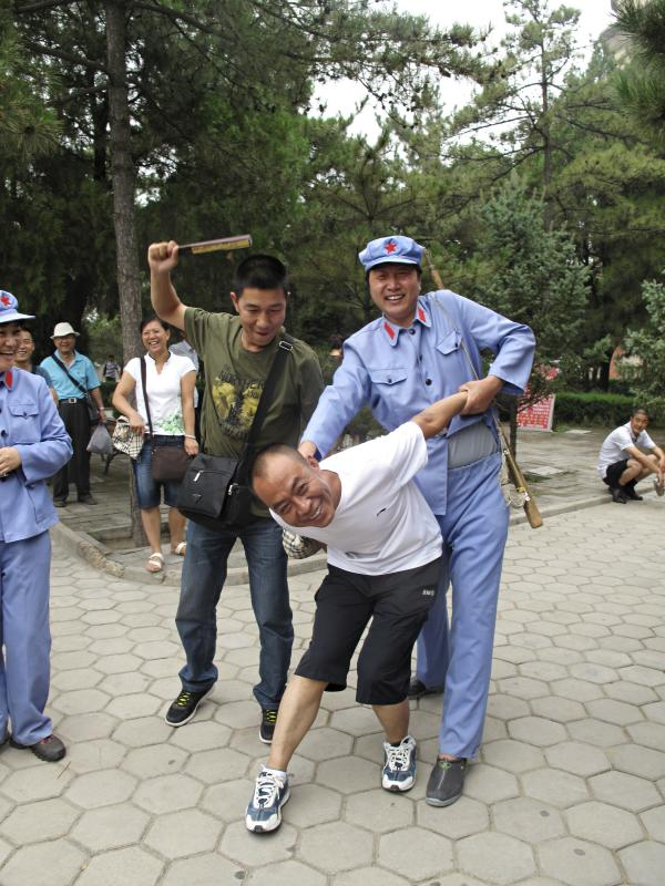 "A tourist with a passing resemblance to Chairman Mao put another visitor in a stress position known as the ""airplane,"" which was often used on ""class enemies"" during the mass upheaval of China's Cultural Revolution, from 1966 to 1976."