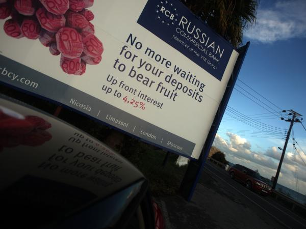 A car drives past a billboard promoting a Russian bank on a main road in the southern Cypriot port of Limassol earlier this month. Russian and Ukrainian investors have a major presence in Cyprus.